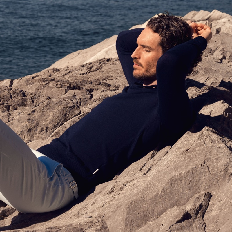 Relaxing, Justice Joslin sports a navy Thunderball polo $475 from Orlebar Brown's 007 collection.
