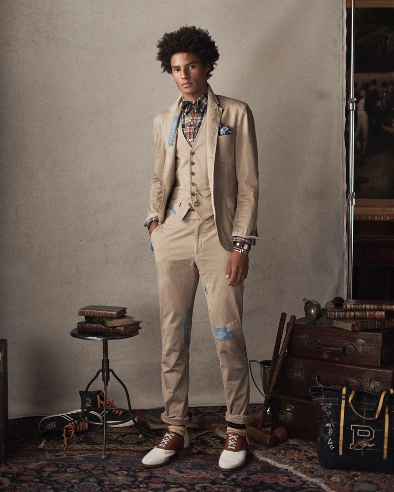 Johair Dramiga dons a neutral-colored three-piece suit with a plaid shirt and bow-tie by POLO Ralph Lauren.