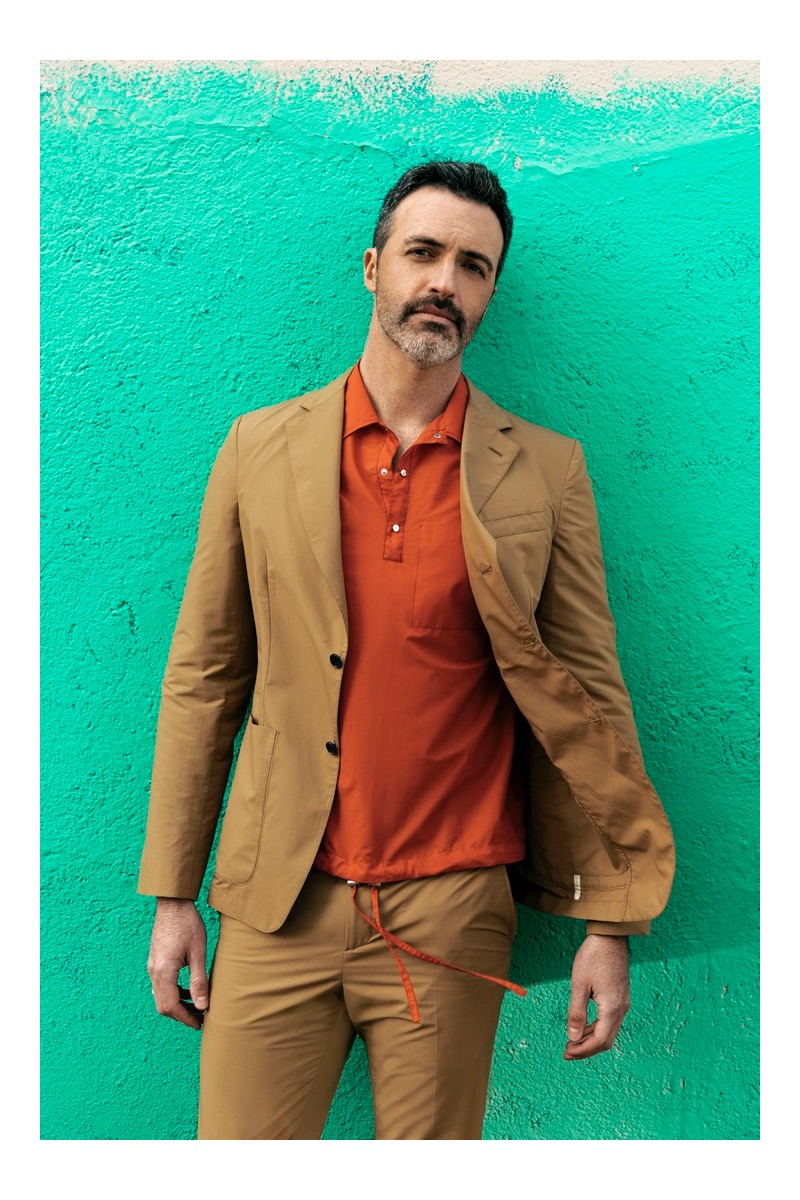 Front and center, Reid Scott wears a shirt and suit by Salvatore Ferragamo.