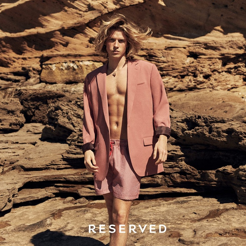 Wearing an oversized jacket, Biel Juste also sports swim shorts by Reserved.