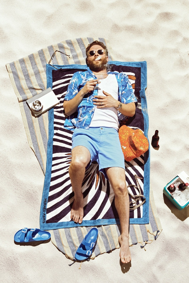 Relaxing on an Hermès beach towel, Seth Rogen wears a Dior Men shirt, Calvin Klein tank, POLO Ralph Lauren shorts, Birkenstock sandals, and Garrett Leight sunglasses.