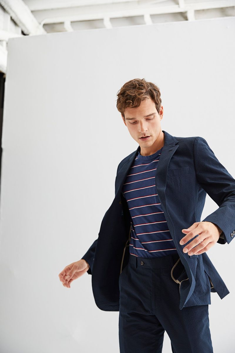 A smart vision, Alexandre Cunha dons a Todd Snyder Black Label seersucker Sutton suit $1,046 in navy with a short-sleeve stripe t-shirt $88 in navy.