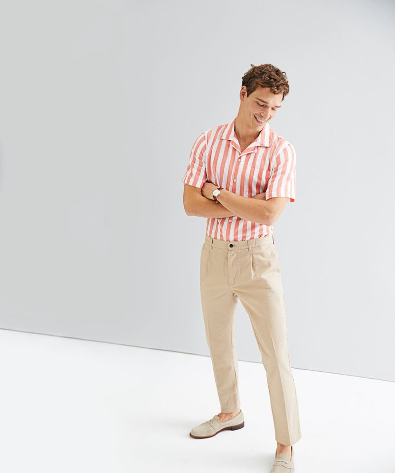 All smiles, Alexandre Cunha wears a Todd Snyder short-sleeve camp collar bold stripe shirt $158 in coral with linen Sutton suit trousers $228 in beige.