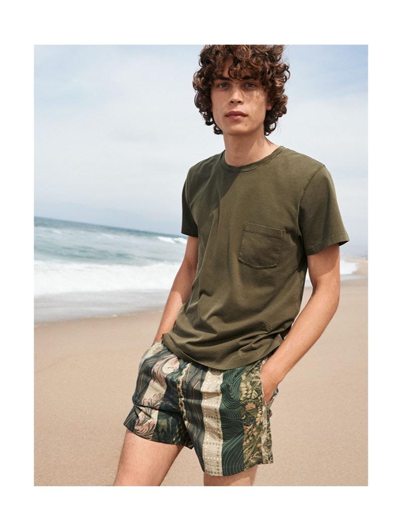 Hitting the beach, Lucas Bin sports military green Dries Van Noten swim shorts $244.
