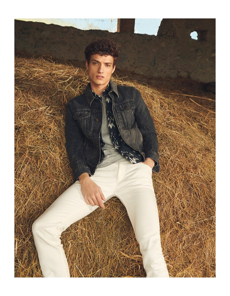 Laying in the hay, Serge Rigvava wears a Saint Laurent denim jacket with white jeans by Burberry.