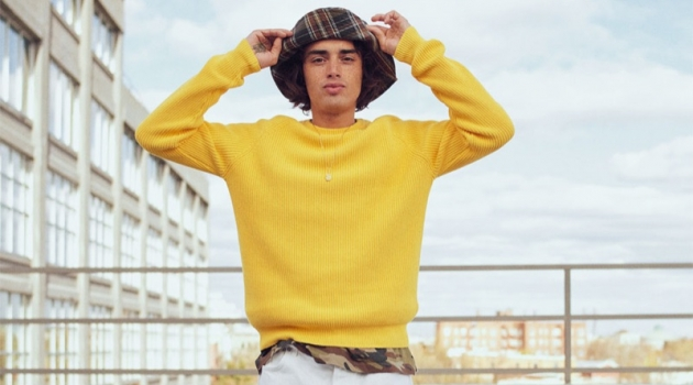 Naleye Dolmans sports a yellow ribbed sweater with a camouflage t-shirt, plaid bucket hat, and pants from Zara.