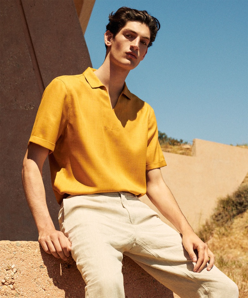 Aaron Shandel sports a yellow polo shirt and linen pants by Zara.