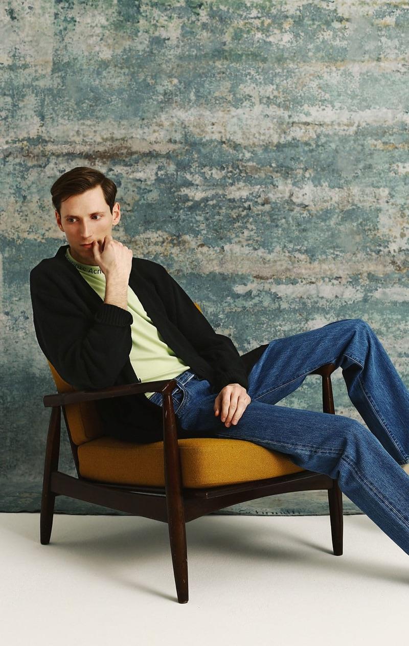 Relaxing, Bastiaan Ninber models a Raey cqshmere cardigan, Acne Studios t-shirt, and Prada jeans.
