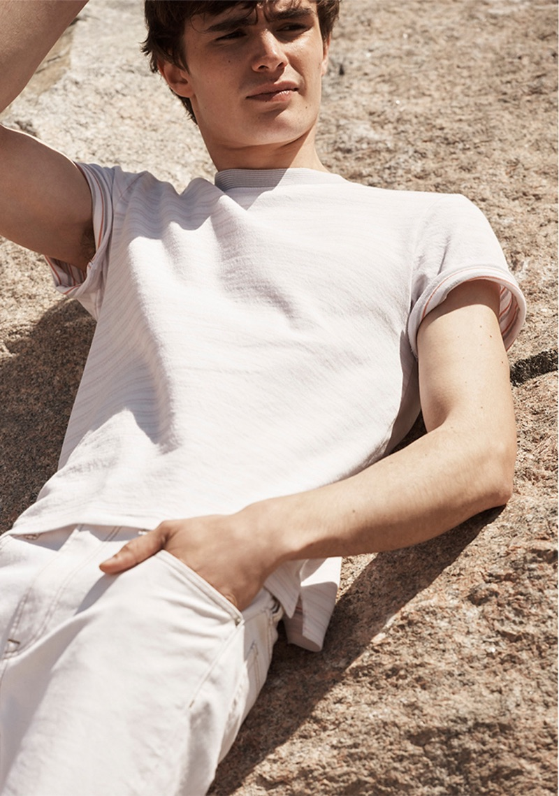 Laying out, Liam Little rocks a Club Monaco multi-stripe tee $59.50 and cropped straight jeans $129.50.
