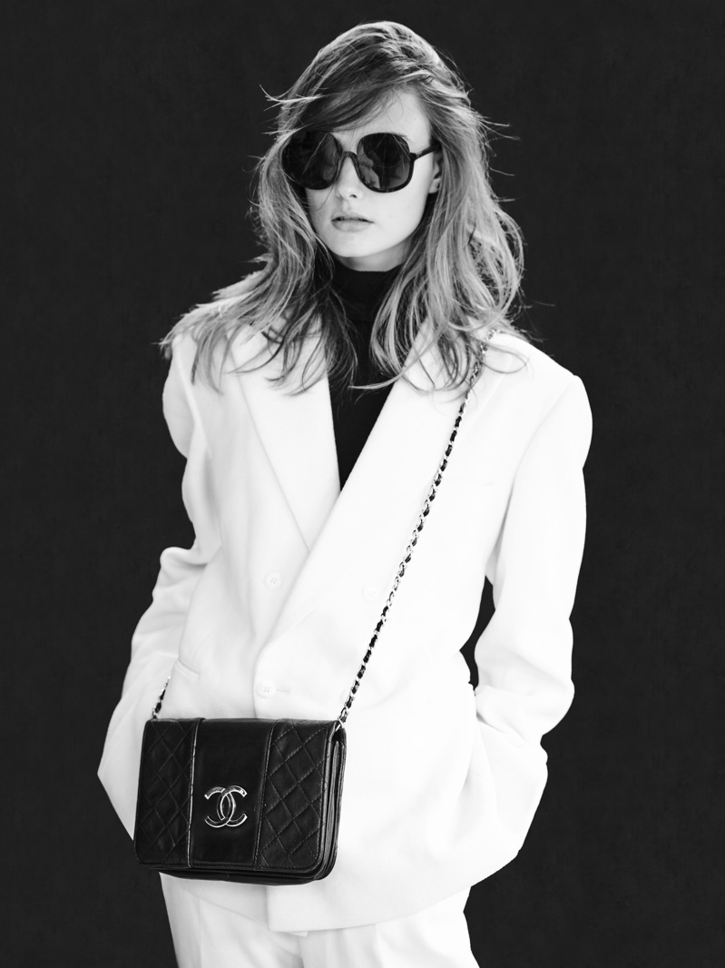 Chic in white, Erin Heart models a tailored look by Helen Anthony. She also wears a Chanel bag and Delirious Eyewear sunglasses.