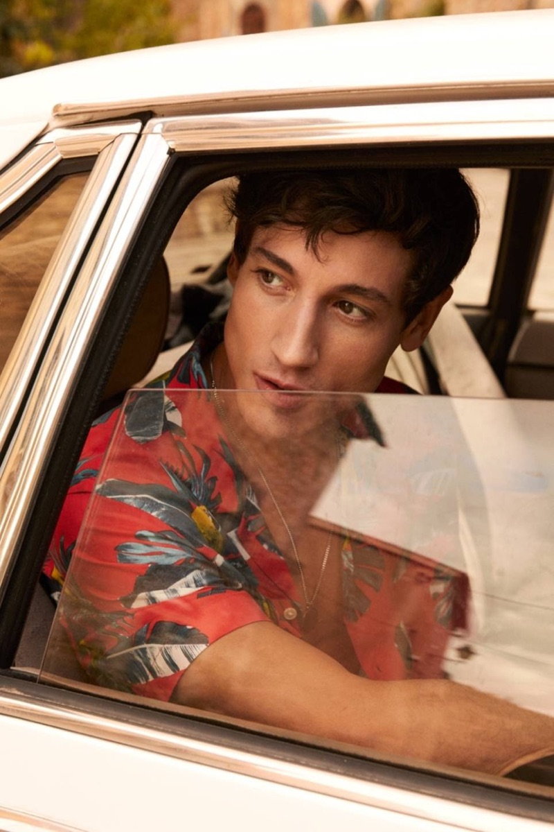 On the move, Nicolas Ripoll sports a red palm print resort shirt $17.99 from H&M.