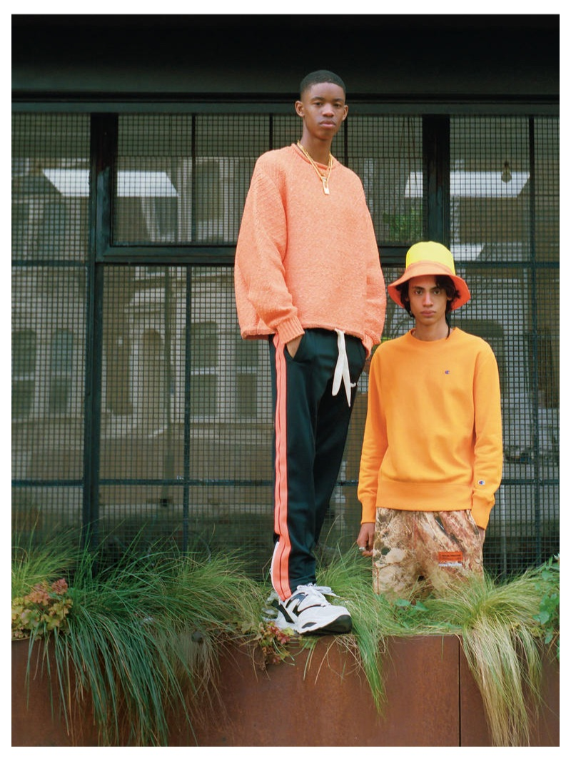 From left, Montell wears ACNE STUDIOS sweater £430; PALM ANGELS track pants £285; VERSACE necklace £370; HERON PRESTON padlock necklace £245; DSQUARED2 trainers from a selection; Benjamin wears CHAMPION sweatshirt £76.95; HERON PRESTON trousers £310; DSQUARED2 hat £215; GIVENCHY ring £240