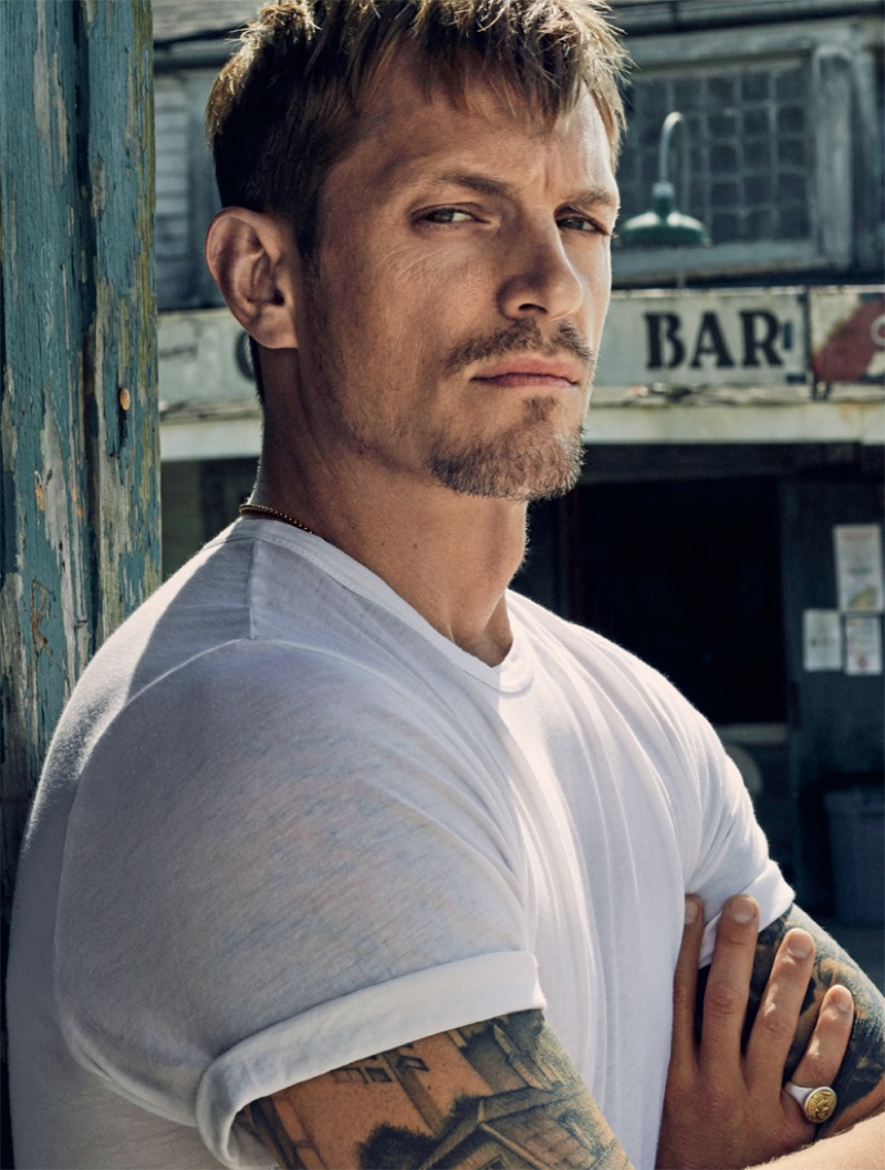 Front and center, Joel Kinnaman sports a white t-shirt in a striking photo.