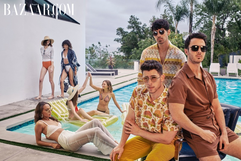 Relaxing poolside, Nick Jonas wears a Bode shirt, Missoni pants, and Giorgio Armani sunglasses. Joe Jonas dons a Missoni cardigan and pants with Etro green loafers and (SALT) sunglasses. Kevin Jonas sports a Mr. Turk jumpsuit and M2M sunglasses with a David Yurman necklace and ring.