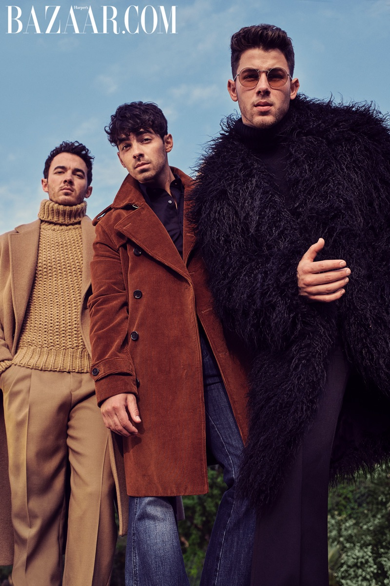 Tapping into retro style, Kevin Jonas wears a Michaels Kors camel coat, turtleneck and pants. Joe Jonas dons a Michael Kors cognac corduroy coat, black shirt and denim jeans. Meanwhile, Nick Jonas wears a  Michael Kors black coat, turtleneck and pants with Valentino sunglasses.