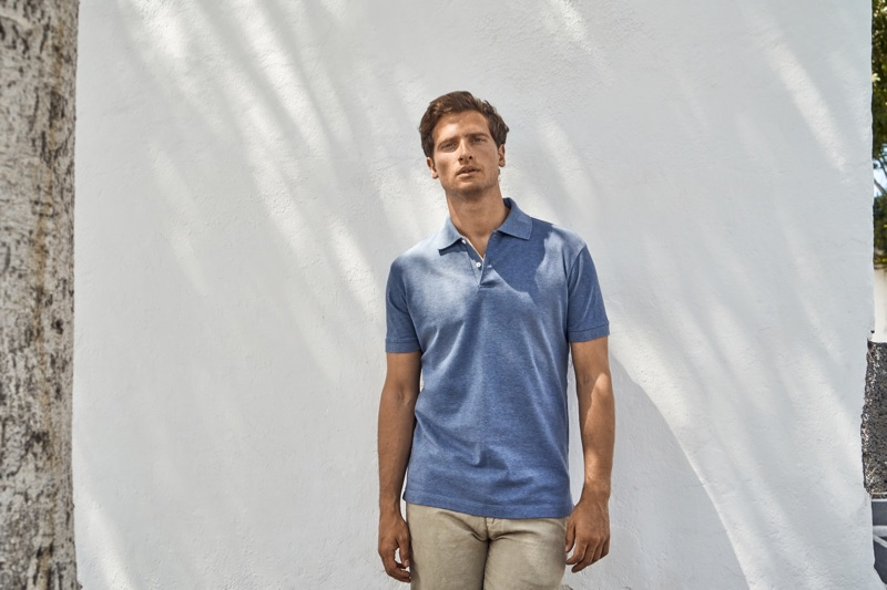 Front and center, Tom Warren dons a steel blue polo from Luca Faloni.