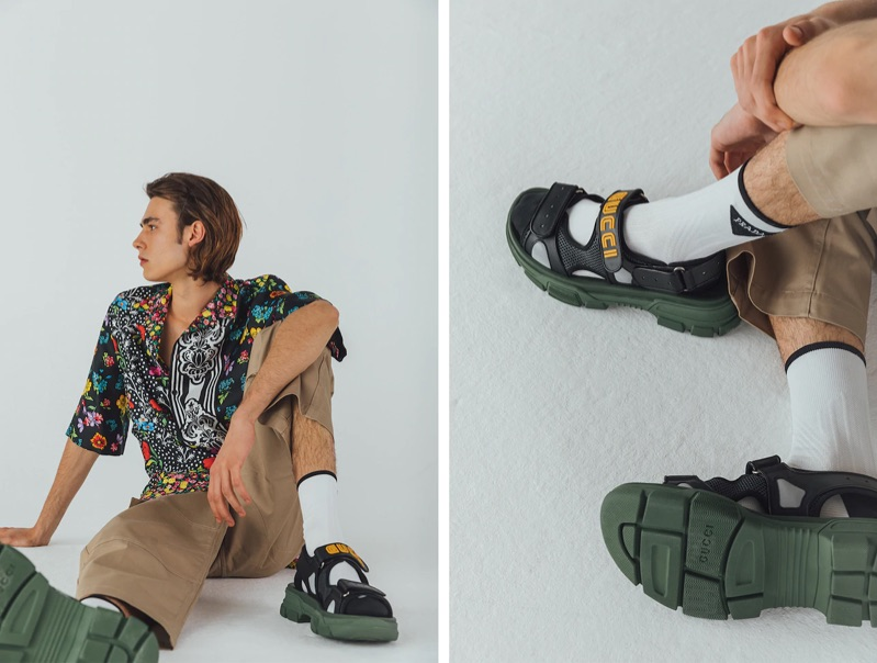 Taking to the studio, Michele Lanotte sports a Versace floral print silk bowling shirt $1,550, Jacquemus cargo pants $254, Valentino logo socks $125, and Gucci sandals $890.