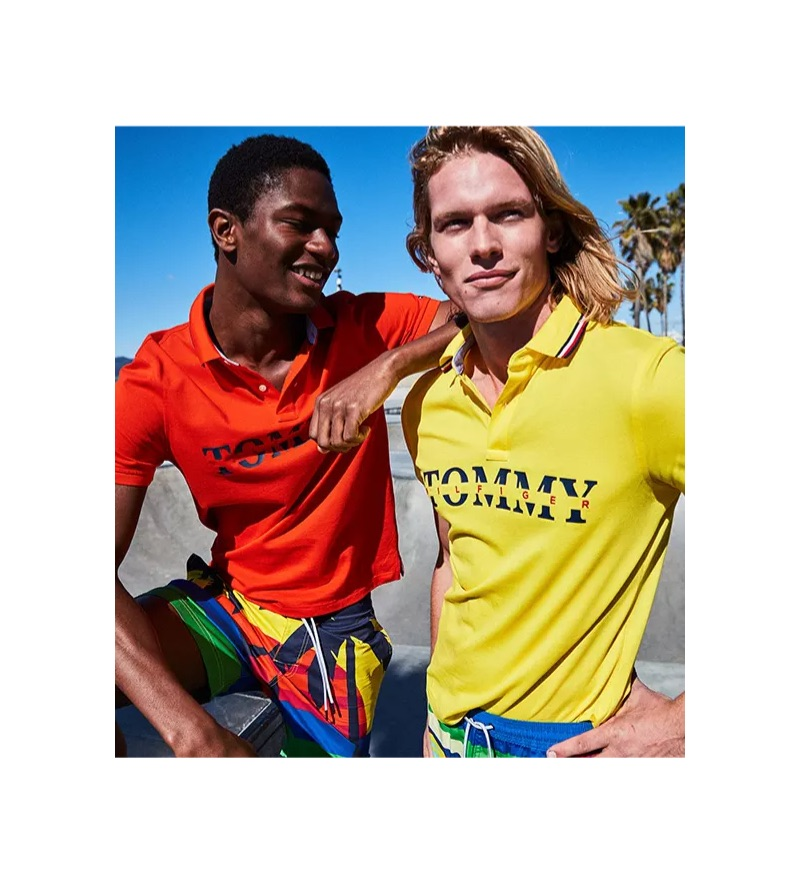 Models Hamid Onifade and Hunter Bach wear colorful Tommy Hilfiger logo polo shirts $59.50.