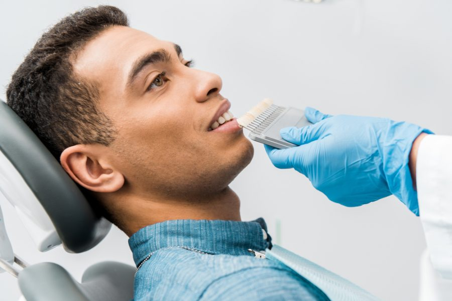 Man Comparing Teeth Shades at Dentist