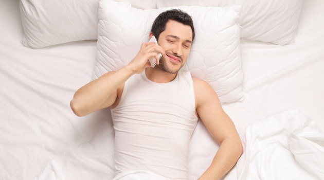Man in Bed Talking on Phone