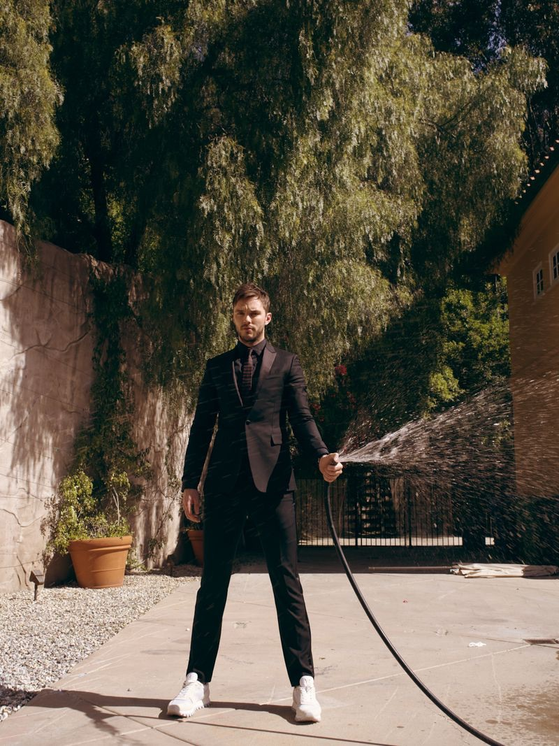 An elegant vision, Nicholas Hoult dons a Berluti shirt and tuxedo with a Celine tie and Louis Vuitton sneakers.