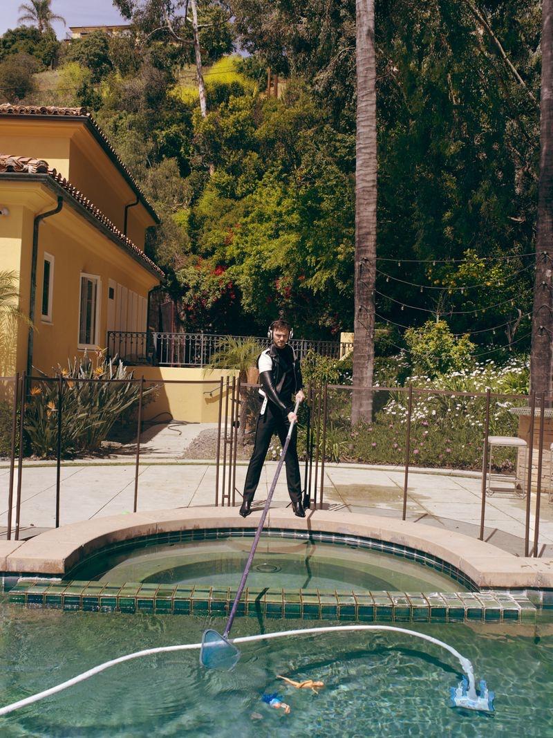 Tending to the pool, Nicholas Hoult wears Celine.