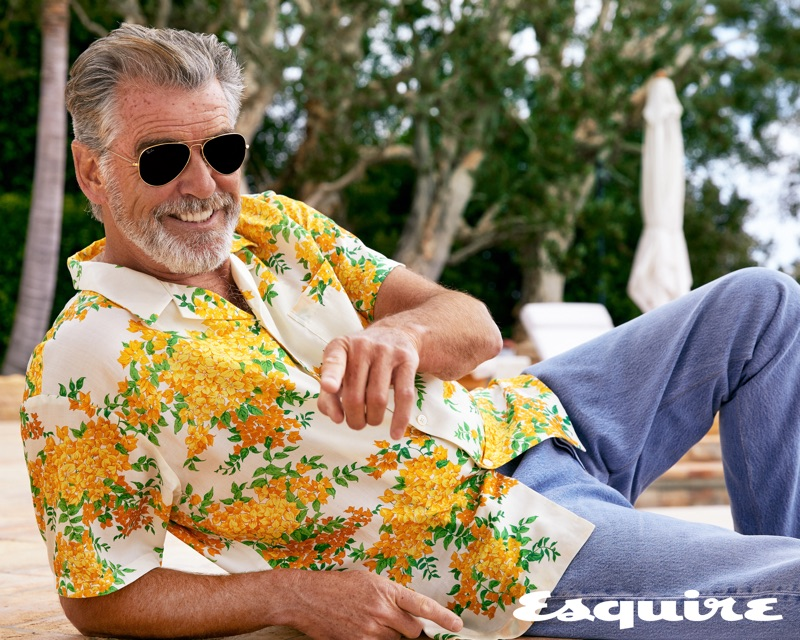 Embracing summer style, Pierce Brosnan sports a John Elliott shirt, vintage Levi's jeans, and Ray-Ban sunglasses.