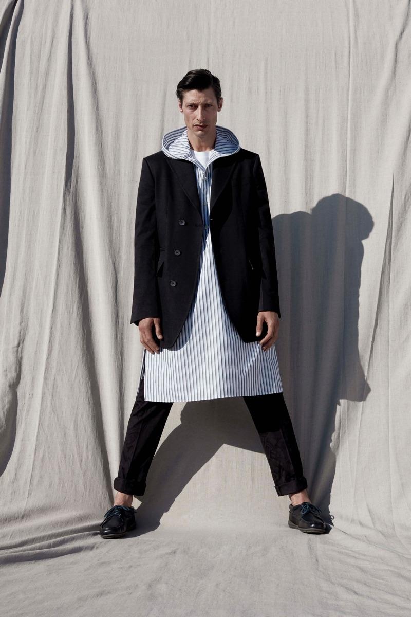 Jonas Mason sports a hooded tunic with an elegant blazer from Salvatore Ferragamo.