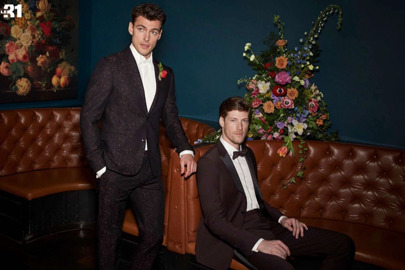 Dressed to impress, Filip Wolfe and Alex Loomans charm in sharp looks from Simons. Left: Filip dons an iridescent burgundy floral jacquard suit with a white shirt by LE 31. Right: Alex wears a burgundy tuxedo with a piped shirt and bow-tie by LE 31.