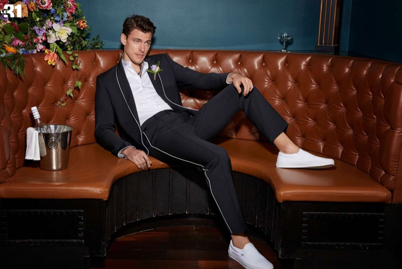 Making a clean statement, Filip Wolfe wears a piped suit jacket and pants with an officer collar shirt by LE 31. White Vans classic slip-ons complete his look.
