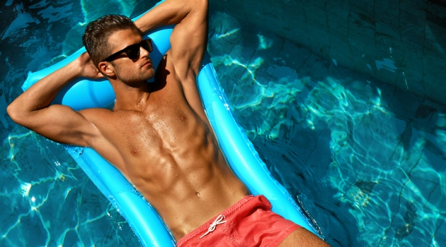 Tan Male Model in Sunglasses and Swim Shorts in Pool
