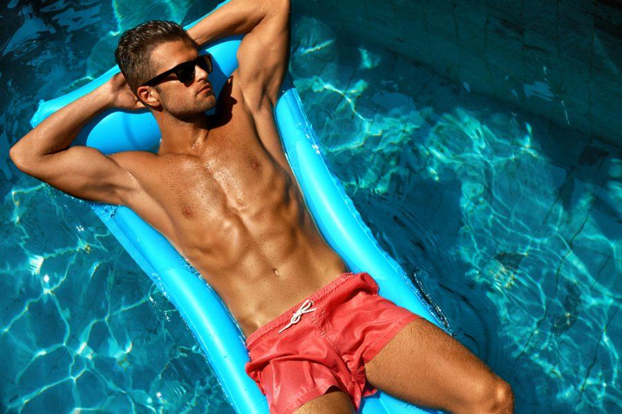 Tan Male Model in Sunglasses and Swim Shorts in Pool