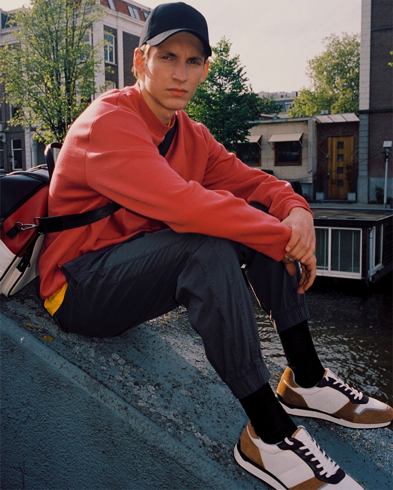 Giel Dils wears a red sweatshirt, poplin pants, sneakers, and accessories from Zara.