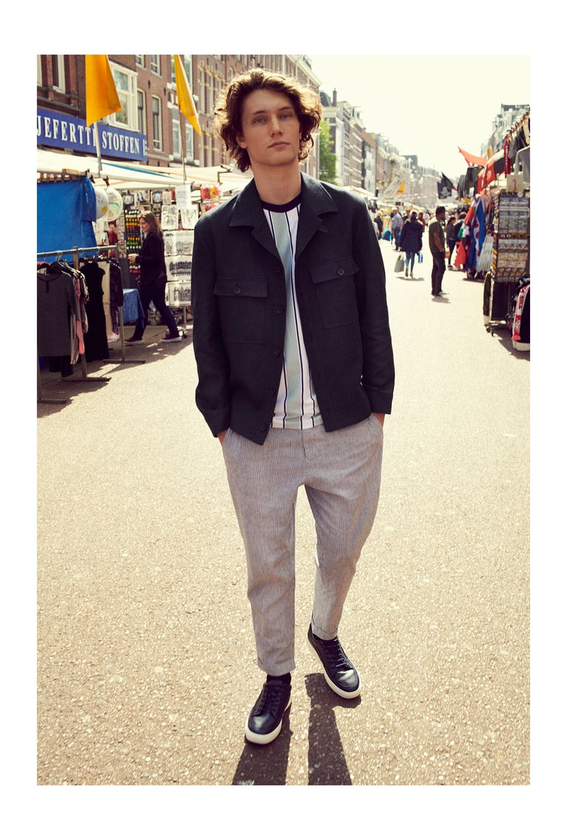 Johannes Spaas steps out in a smart jacket, vertical striped t-shirt, pants, and sneakers from Zara.