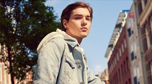 Felix Prabitz sports a denim jacket with a hooded sweatshirt, jumpsuit, and sneakers by Zara.