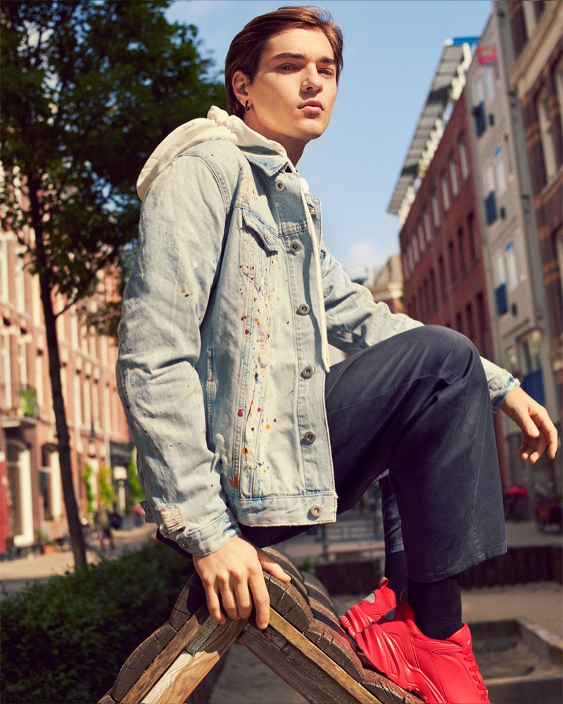 Felix Prabitz sports a denim jacket with a hooded sweatshirt, jumpsuit, and sneakers by Zara.