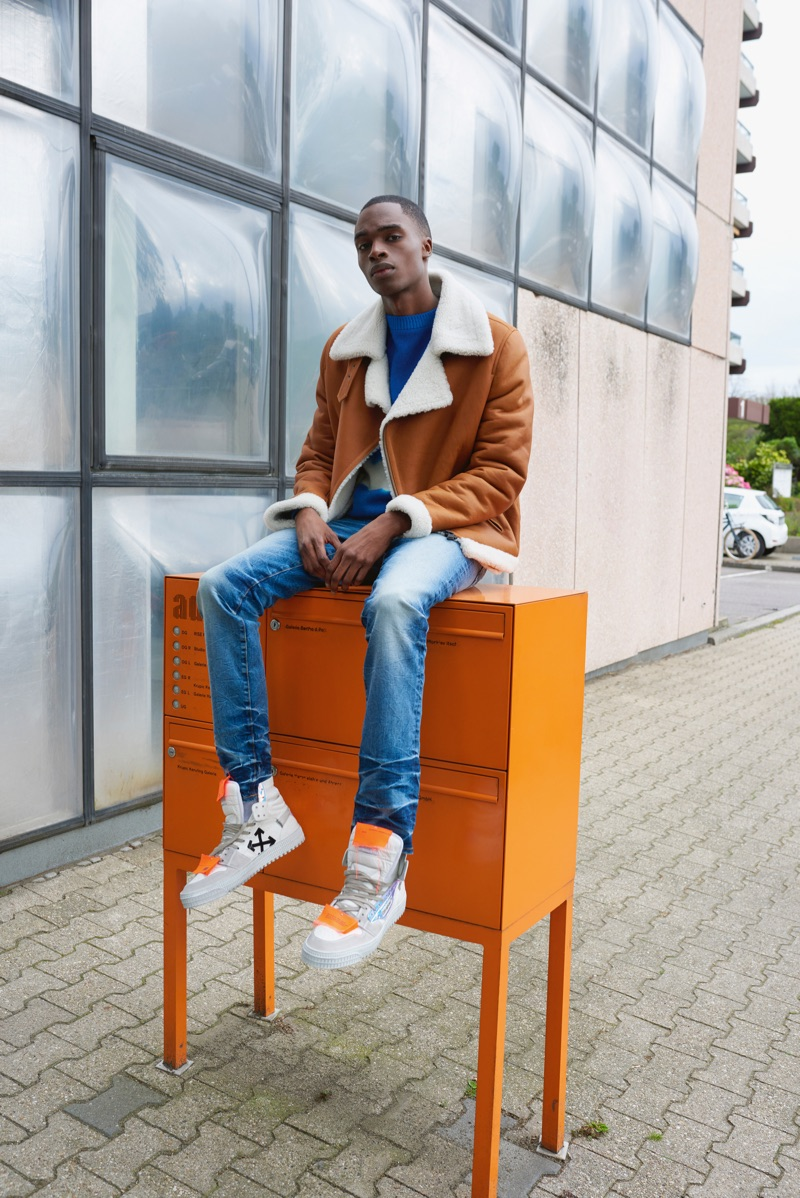Going casual, Bakay Diaby models a Benedetta Novi jacket with a sweater by The Elder Statesman. He also sports AMIRI jeans and Off-White sneakers.