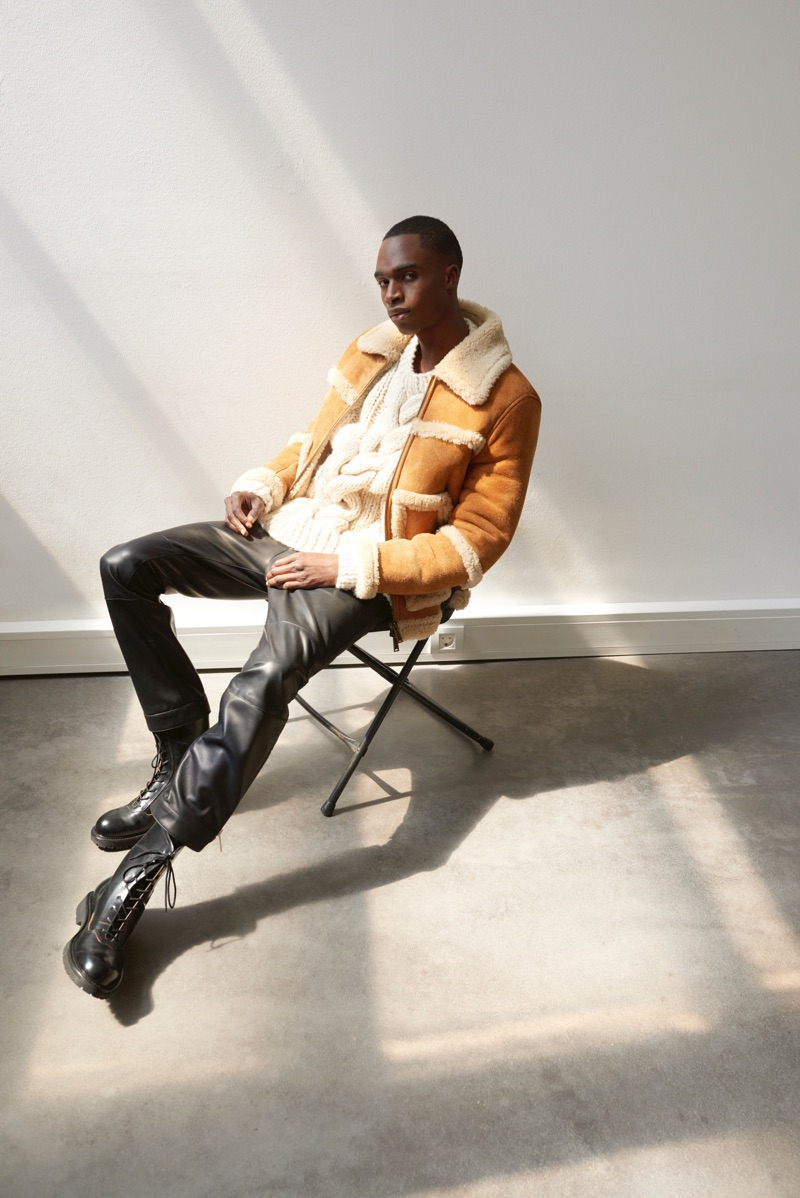 Retreating indoors, Bakay Diaby dons a shearling jacket, sweaters, and pants by Dsquared2. Off-White boots complete his look.
