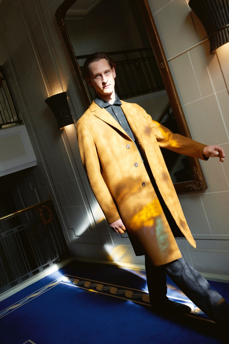 On the move, Rogier Bosschaart dons a Harris Wharf coat with a polo and pants by Giorgio Armani.