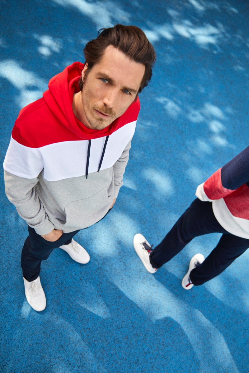 Going sporty, Guillaume Macé rocks a block-striped hoodie with skinny jeans from Esprit.