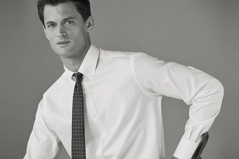 Captured in a black and white photo, Garrett Neff wears a shirt and tie from Massimo Dutti.