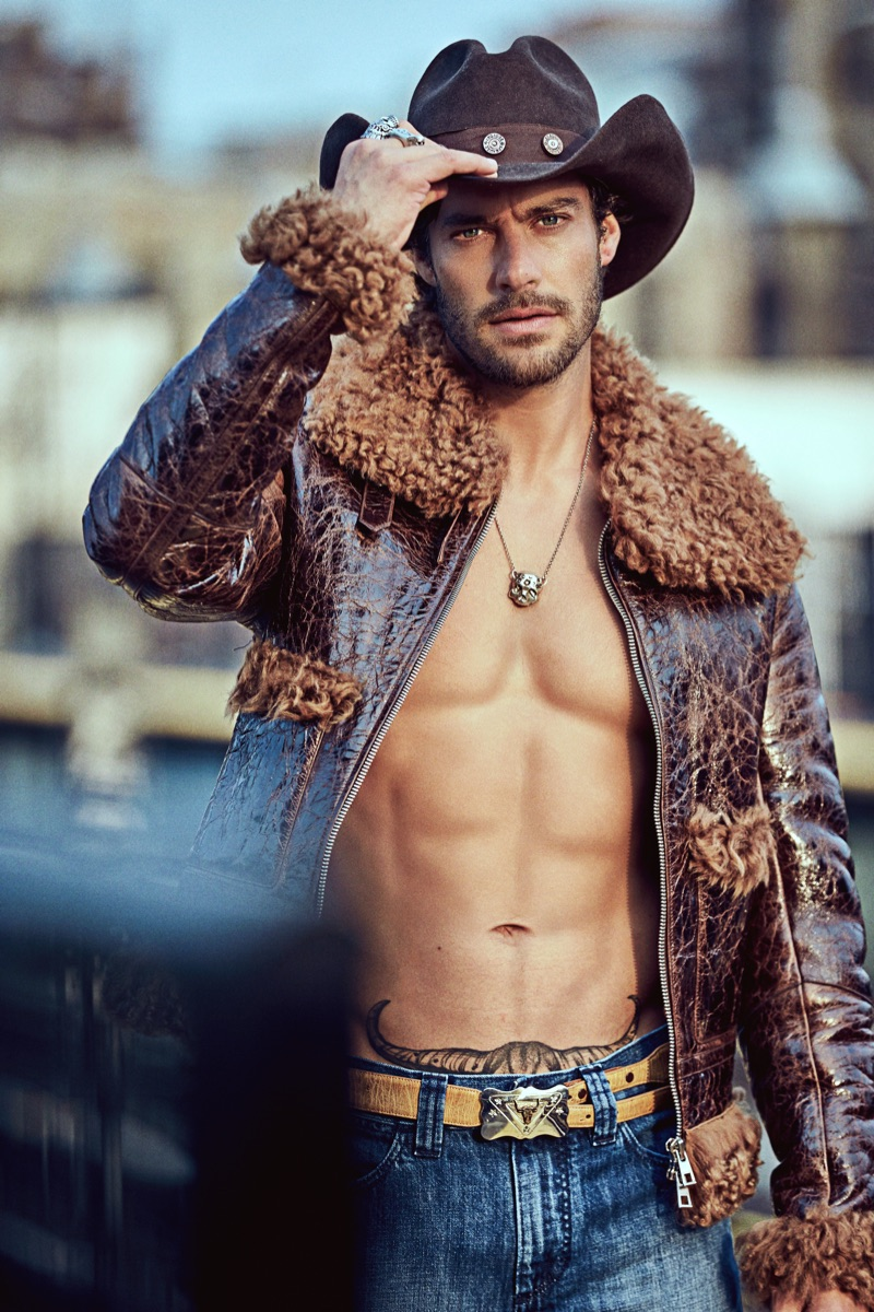Gonçalo wears hat and belt Space Cowboy, necklace and rings Britt Bolton Jewelry, jacket and jeans Michael Kors Collection.