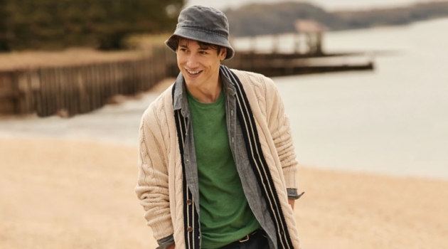 "All smiles, Nicolas Ripoll wears a J.Crew cable-knit cardigan $125, chambray shirt $79.50, t-shirt $19.50, 10.5"" chino shorts $65, and a bucket hat $39.50."