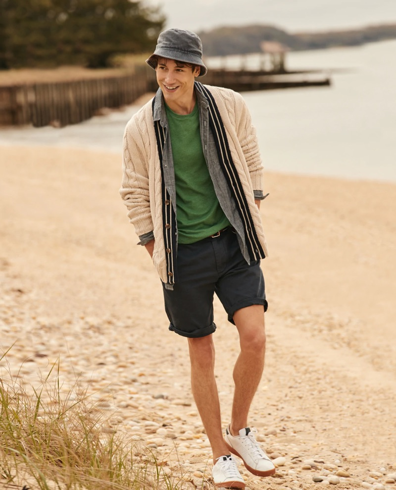 """All smiles, Nicolas Ripoll wears a J.Crew cable-knit cardigan $125, chambray shirt $79.50, t-shirt $19.50, 10.5"""" chino shorts $65, and a bucket hat $39.50."""