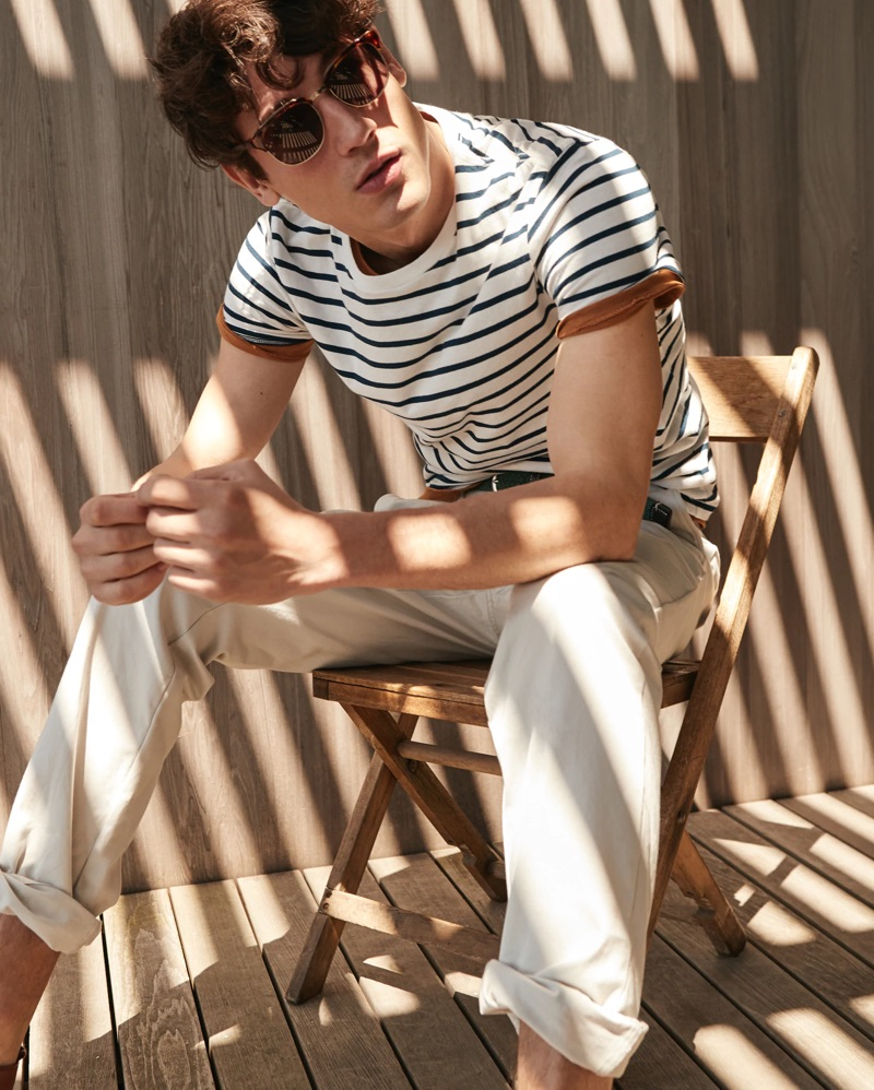 Relaxing, Nicolas Ripoll dons a J.Crew striped t-shirt $24.50, copper pocket tee $29.50, and 770 straight-fit chinos.