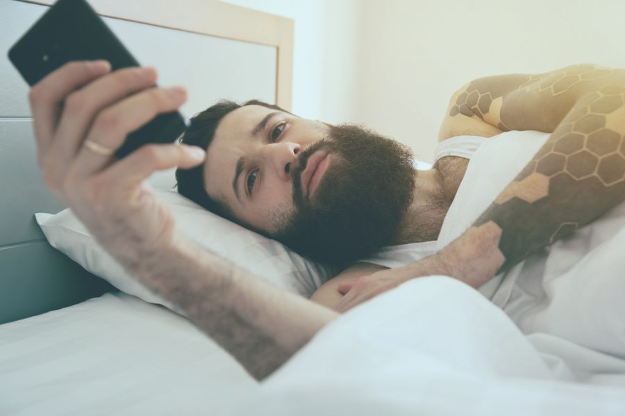 Man with Beard in Bed Taking Selfie on Phone