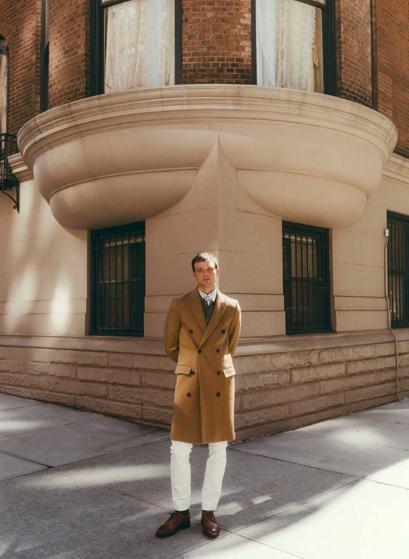 A chic vision, Rocky Harwood dons a Salle Privée coat, sweater, and trousers. A Paul Smith shirt and Cheany shoes complete his look.