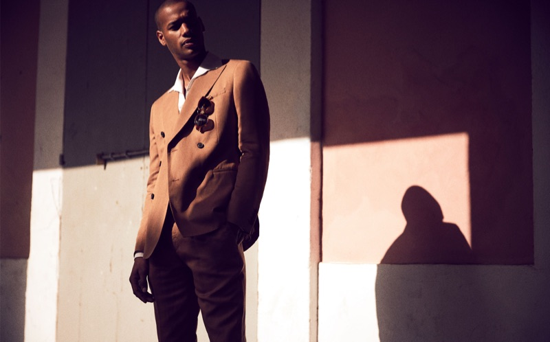 Embracing brown, Sacha M'Baye is sharp in a double-breasted suit by Reiss.
