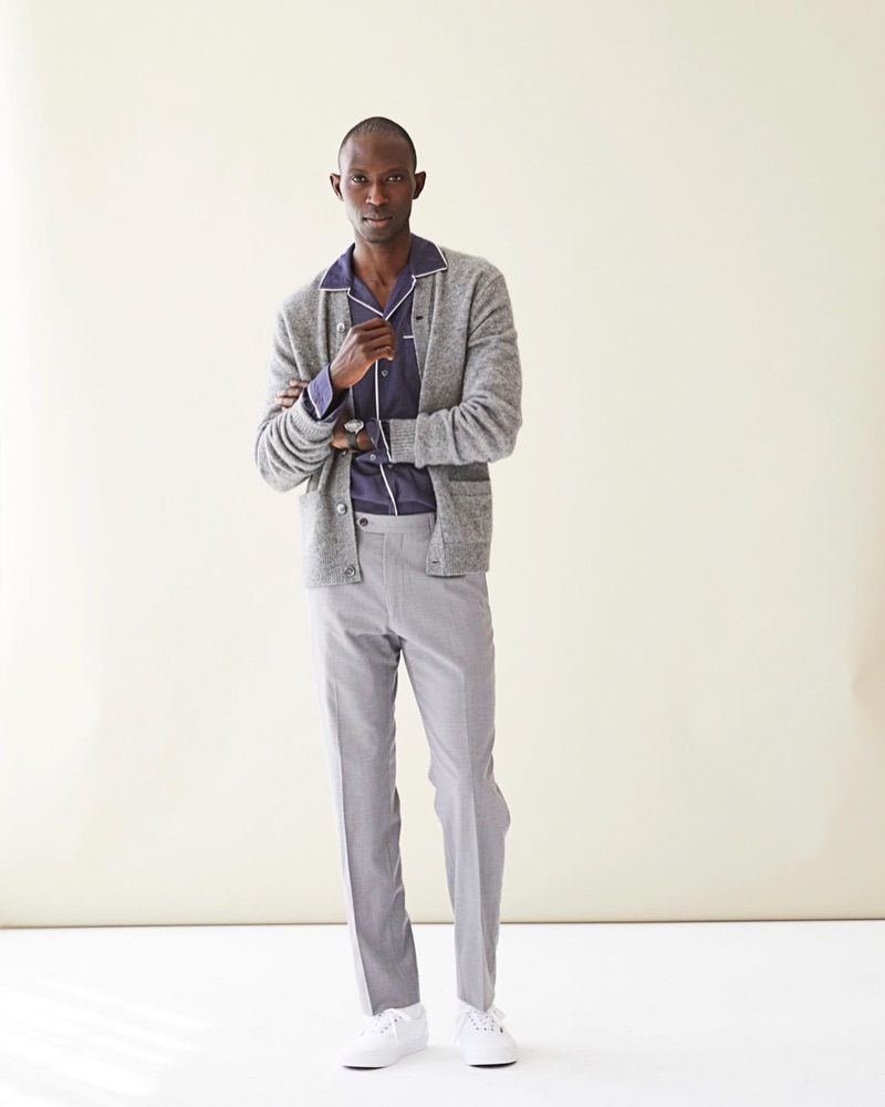 Model Armando Cabral sports a Todd Snyder long-sleeve camp collar tipped navy shirt $228 with a cardigan and trousers.