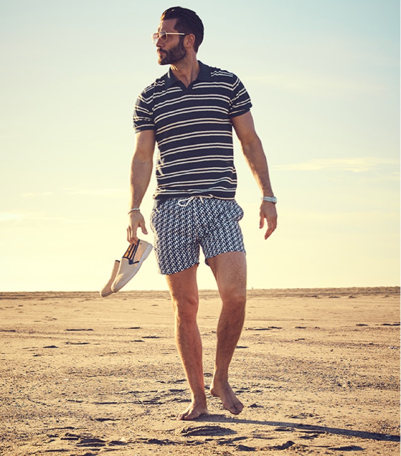 Summer Polo: Life may not actually be a beach, but with the right polo, it can sure feel like it. Taking to the beach, John Halls wears Todd Snyder's striped bouclé polo $139 in navy with Hartford geometric print swim shorts $198.